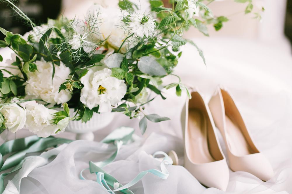 Buquê de flores brancas sob um lençol de seda branco e um scarpin branco ovo