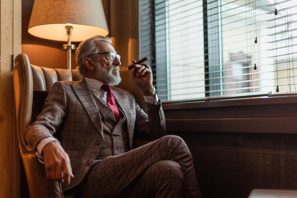 Homem de terno fumando charuto