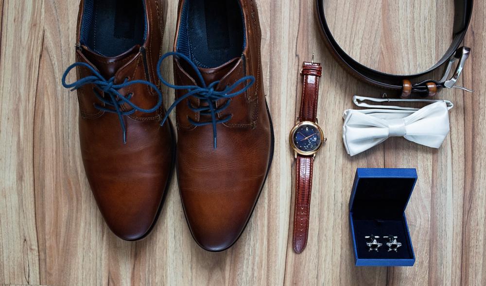 Sapato social marrom com cardaço azul, relógio marrom com pulseira fina, gravata branca de borboleta, cinto enrolado e caixa azul com duas abotoaduras de prata em formato de estrela