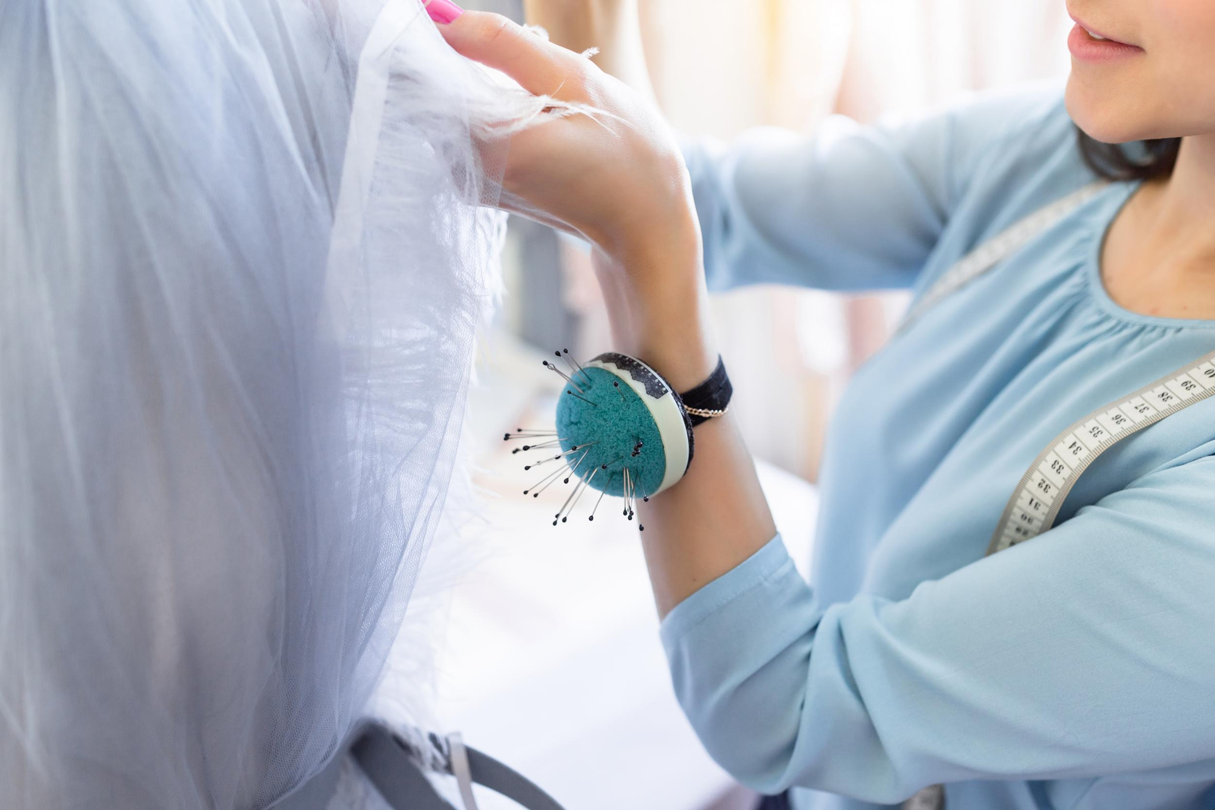 Costureira tirando medidas para vestido