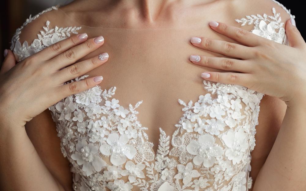 Pessoa com mãos ao colo em um vestido de renda bordado de flores branco