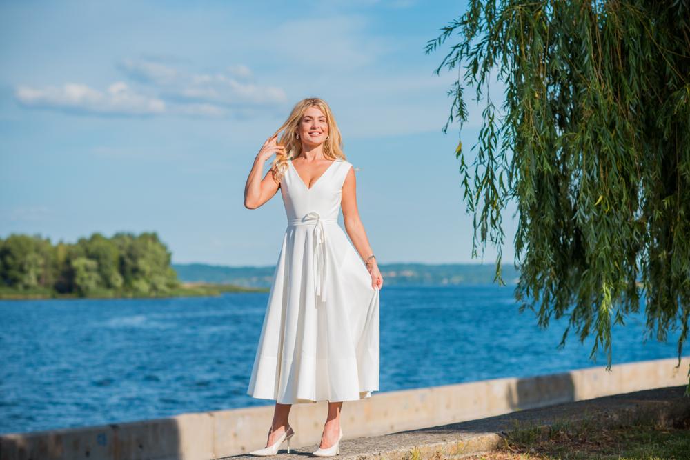 Mulher com vestido midi branco em um pier, com o mar ao fundo