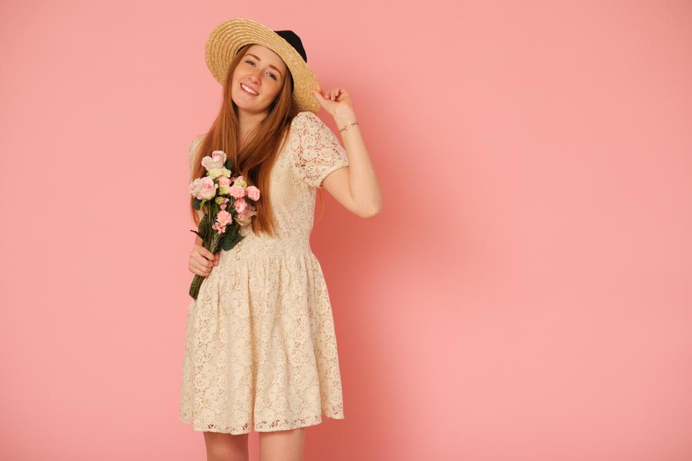 Pessoa com vestido e chapéu de palha, segurando buquê de rosas